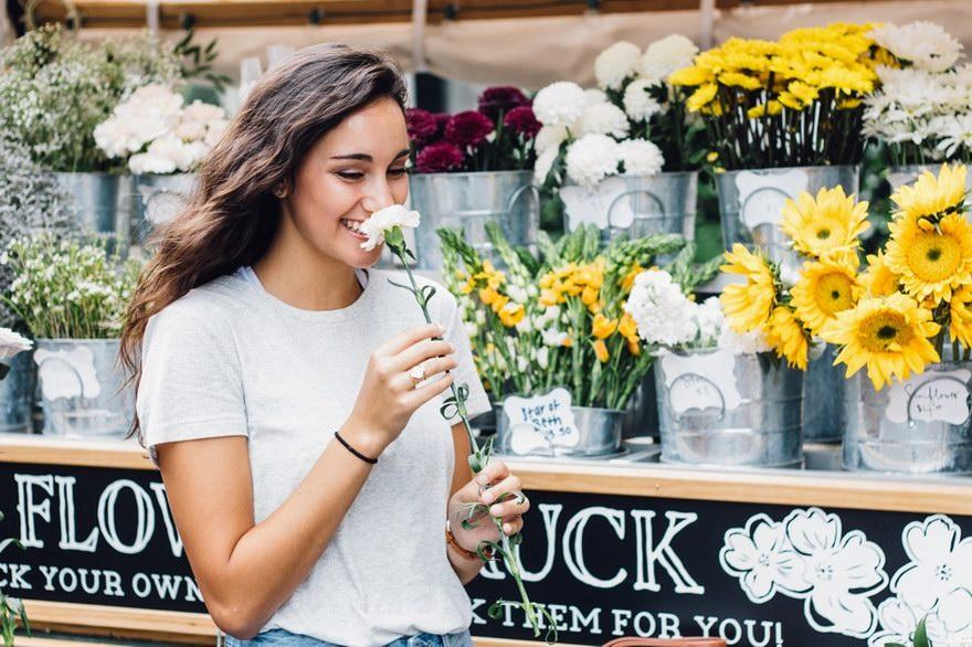 Dobra decyzja po wyborze pożyczki. Uśmiechnięta kobieta wąchająca kwiatek.